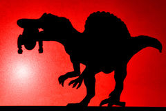 Spot light projection shadow of a spinosaurus with a dead body Royalty Free Stock Images