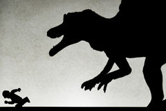 Spot light projection shadow of a spinosaurus toy chasing a running human Royalty Free Stock Images