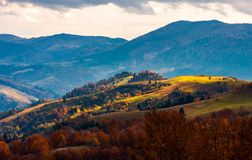 Spot of light on a rolling hills. Beautiful countryside in mountains. dramatic autumn weather Stock Images
