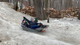 Cheerful children slide down the snow on a sled. Moscow, Russia, February 2019. stock video footage
