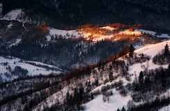 Spot of morning light on hillside with forest. Beautiful mountainous scenery in winter stock photo
