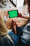 Spot omhoog - het groene scherm op tabletapparaat, Jong paar die op t letten royalty-vrije stock afbeeldingen