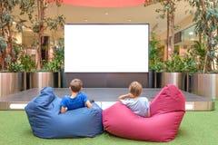 Spot omhoog Het lege reclamescherm in modern winkelcomplex Kinderen die het grote lege digitale scherm bekijken Stock Foto