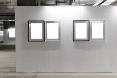 Spot omhoog Lege omlijstingen op witte muur Galerijmuur met lege kaders binnen Royalty-vrije Stock Afbeelding