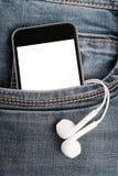 Spot omhoog met moderne smartphone en oortelefoons in jeanszak royalty-vrije stock foto