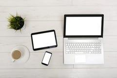 Spot omhoog op een lijst met laptop, tablet, smartphone en een kop van stock foto