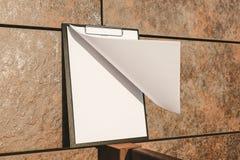 Spot omhoog van de tablet voor het document tegen de muur stock fotografie