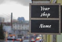 Spot omhoog voor straatwinkel of boutiqueuithangbord De mening van blured straat in een bewolkt weer Royalty-vrije Stock Foto's