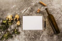 Spot op malplaatje met verwelkte bloemen van witte rozen met een schone envelop, een blocnote en een kop van koffie op een grijze stock foto