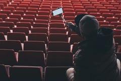 Spot op Smartphone met een selfiestok in de handen van een mens op de achtergrond van de tribunes De kerel neemt een selfie bij royalty-vrije stock afbeeldingen