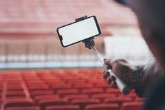 Spot op Smartphone met een selfiestok in de handen van een mens op de achtergrond van de tribunes De kerel neemt een selfie bij stock afbeelding