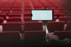 Spot op Smartphone met een selfiestok in de handen van een mens op de achtergrond van de tribunes De kerel neemt een selfie bij stock foto