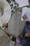 Spot op werkruimte met hoed, pen, jeans, document, tegenhanger, shell, bloemen, stuk speelgoed, en blocnote op lichtbruine achter royalty-vrije stock afbeeldingen
