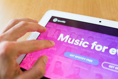 Spotify. Man's hand use with his fingers tablet. Spotify app on the screen. Spotify is service for streaming and listening music on internet stock images