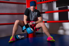 Spotive young male boxer sitting near red corner and puts on box stock photos