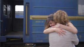 Spotkanie kochający ludzie, szczęśliwa młoda kobieta ściska samiec i śmia się blisko taborowego furgonu na stacji kolejowej po ro zbiory wideo