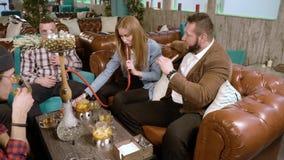 Spotkanie przyjaciele M?odzi ludzie dymi nargile i odpoczywa w kawiarni zdjęcie wideo