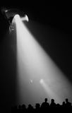Spotlight on Audience. Big spotlight on people / audience silhouettes at a concert Royalty Free Stock Photography