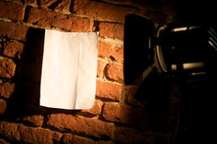 Spotlight on blank wall poster. A view of a bright spotlight shining directly on a blank poster or sign on a brick wall at night Royalty Free Stock Photography