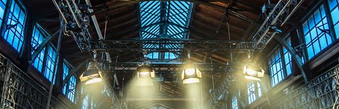 Spotlight on the ceiling of a former factory hall for lighting d. Uring a concert with rock music Stock Image