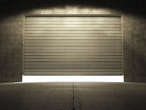 Spotlight illuminate building of grungy concrete. With roll up door Stock Images