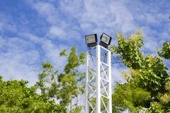 Spotlight pole with green tree With blue sky.  Royalty Free Stock Photo