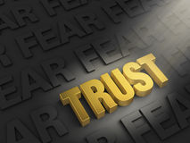 Spotlight On Trust Not Fear. A spotlight illuminates a bright, gold TRUST on a dark background of FEARs Stock Photos
