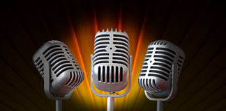 Spotlight on vintage mics. Photo of spotlight on trio of vintage mics with art deco background stock image