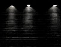 Spotlights on a black brick wall. Highly contrasted spotlights on an outdoor black brick wall Stock Images