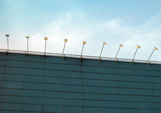 Spotlights, factory exterior. A row of spotlighting equipment on the exterior wall of an industrial factory building in an industrialized estate.  Taken against Stock Photos