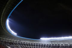 Spotlights and floodlights at a stadium at night. With fans watching game stock image