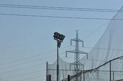 Spotlights post. On blue sky with electric pole on the background royalty free stock images