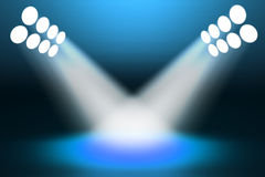 Spotlights shining on the stage. Blue background with lights. Hi-res digitally generated image Royalty Free Stock Image