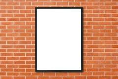 Spott herauf den leeren PlakatBilderrahmen, der am Wandhintergrund des roten Backsteins im Raum hängt - kann verwendeter Spott fü Lizenzfreie Stockbilder