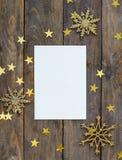 Spott herauf greeteng Karte auf hölzernem rustikalem Hintergrund mit Weihnachtsdekorationsfunkelnschneeflocken und -gold spielt K Stockfotos