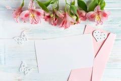 Spott herauf leeres Papier, Postumschlag auf einem wei?en h?lzernen Hintergrund mit nat?rlichen Blumen der rosa Farbe und Schmett lizenzfreie stockfotos
