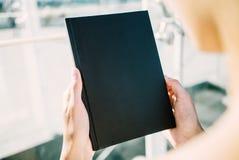 Spott oben des Schwarzbuches in den Händen lizenzfreie stockbilder