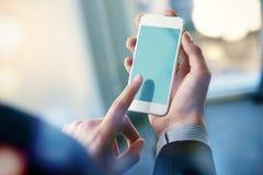 Spott oben eines Mannes, der Smartphone hält Über Weiß lizenzfreie stockfotos