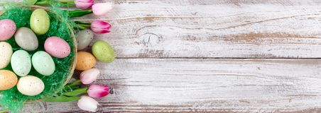 Spotted Easter eggs in basket with tulips on rustic white wooden. Colorful spotted eggs on artificial green grass in basket with tulips for Easter Background Royalty Free Stock Photos