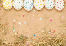 Spotted easter eggs on kraft background with hay Royalty Free Stock Image