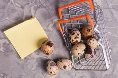 Spotted fresh quail eggs poured out of metal glossy market basket and yellow blank curved paper sticker. On old broken worn gray cement floor stock image