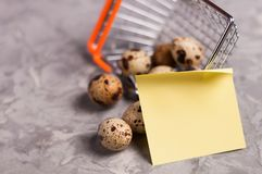 Spotted fresh quail eggs poured out of metal glossy market basket and yellow blank curved paper sticker. On old broken worn gray cement floor royalty free stock images