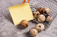 Spotted fresh quail eggs poured out of metal glossy market basket and yellow blank curved paper sticker. On old broken worn gray cement floor stock images
