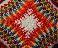 Spotted pattern on the knitted cushion. Knitted multicolored pattern of bright colors on a pillowcase Royalty Free Stock Image