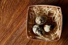 Quail eggs in a box on a rustic wooden background, top view, selective focus. Spotted quail eggs arranged on hay in a box on a rustic wooden background, top Stock Image
