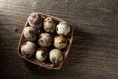 Quail eggs in a box on a vintage wooden background, top view, selective focus. Spotted quail eggs arranged in rows in a box on a vintage wooden background, top Stock Photos