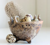 Spotted Eggs. Spotted quail eggs and speckled feather in a small ceramic hand-made bowl stock photography