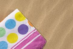 Spotted towel on sand Royalty Free Stock Images