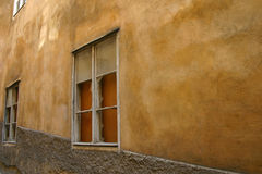 Spotted wall. With windows on alleyway Royalty Free Stock Photo