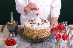 Spotting a Cake Cherry. Close up of a female Pastry Chef spotting a cherry atop a star throne of butter-cream on a decorated cake cake Stock Photos